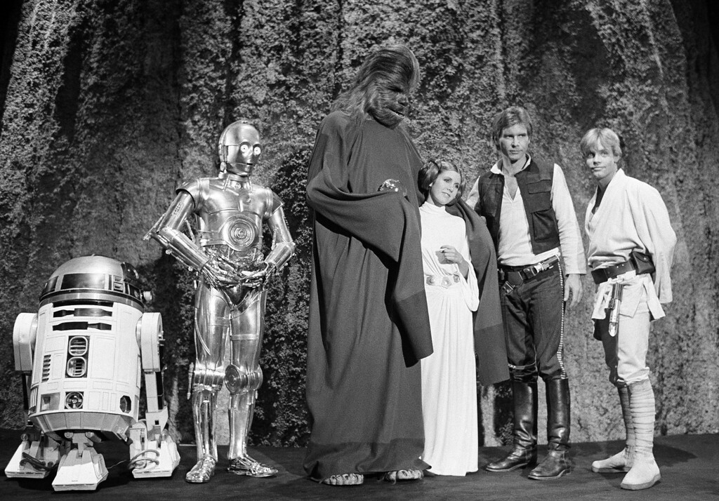 ". FILE - In this Nov. 13, 1978 file photo, shows, from left, Kenny Baker, Anthony Daniels, Peter Mayhew, Carrie Fisher, Harrison Ford, and Mark Hamill during the filming of the CBS-TV special ""The Star Wars Holiday\"" in Los Angeles. On Tuesday, Dec. 27, 2016, a publicist says Fisher has died at the age of 60. (AP Photo/George Brich, File)"