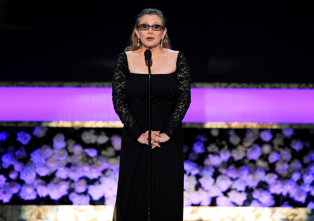 . FILE - In this Sunday, Jan. 25, 2015 file photo, Carrie Fisher presents the life achievement award on stage at the 21st annual Screen Actors Guild Awards at the Shrine Auditorium in Los Angeles. On Tuesday, Dec. 27, 2016, a publicist said Fisher has died at the age of 60. (Photo by Vince Bucci/Invision/AP, File)