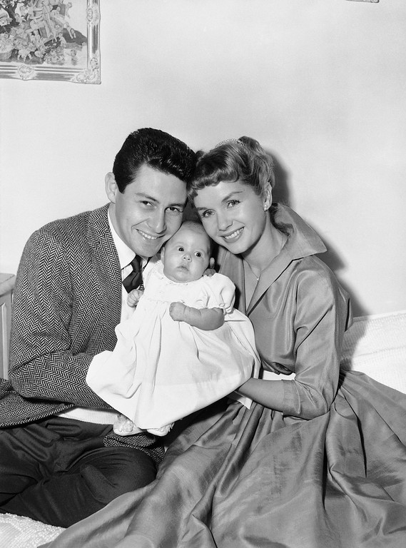 . FILE - In this Jan. 2, 1957 file photo, Eddie Fisher and Debbie Reynolds hold their baby daughter, Carrie Frances Fisher, as the pose for a photo in the Hollywood area of Los Angeles. On Tuesday, Dec. 27, 2016, a publicist says Carrie Fisher has died at the age of 60. (AP Photo, File)