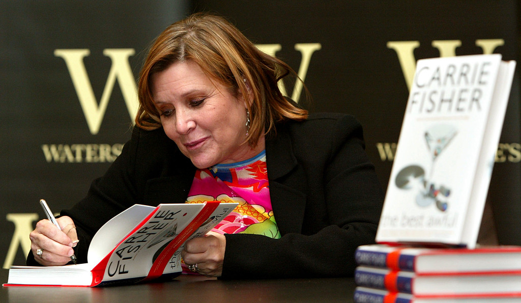 ". FILE - In this Friday, Feb. 20, 2004 file photo, author Carrie Fisher autographs her new book ""The Best Awful\"" at a promotional event in London. On Tuesday, Dec. 27, 2016, a publicist said Fisher has died at the age of 60. (AP Photo/John D. McHugh, File)"