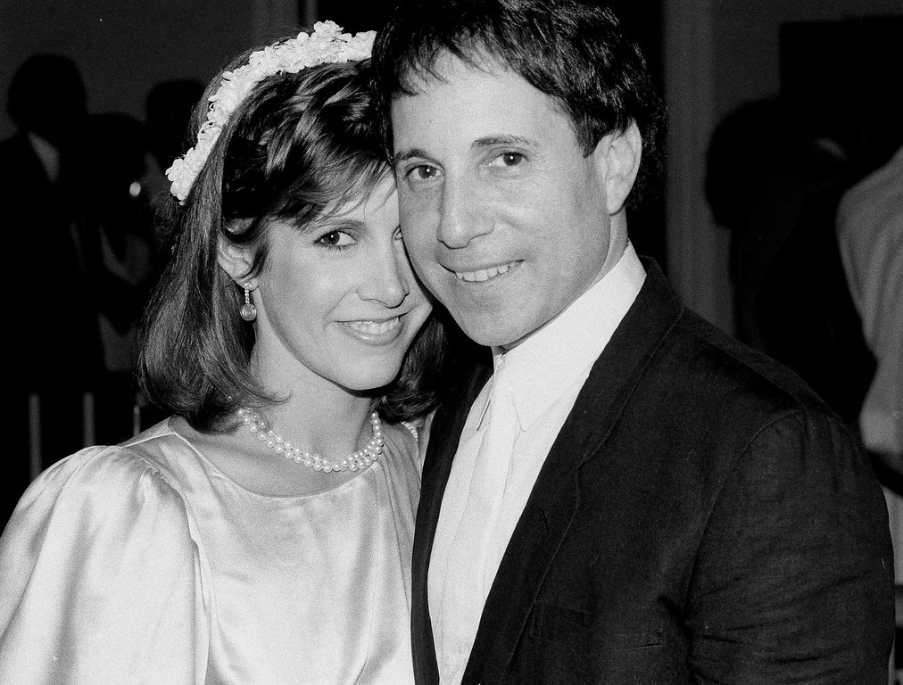 . FILE - In this March 11, 1982 file photo, actress Carrie Fisher and singer-composer Paul Simon leave the Cathedral of St. John the Divine in New York, after a memorial service for comedian John Belushi. On Tuesday, Dec. 27, 2016, a publicist says Fisher has died at the age of 60. (AP Photo/Marty Lederhandler, File)