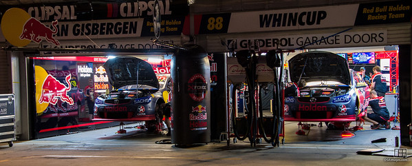 Supercars being worked on at night