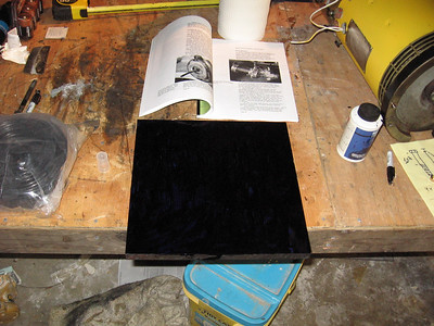 "Coating the plate with blue dye for drill holes. The book that is open is a copy of ""Convert It"", a very popular book for electrical car conversion. You can buy it for about $25.00."