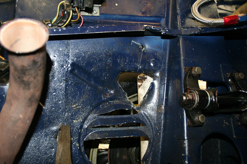 Again, looking from the engine bay out through the hole from the shrapnel and seeing the dented shock.