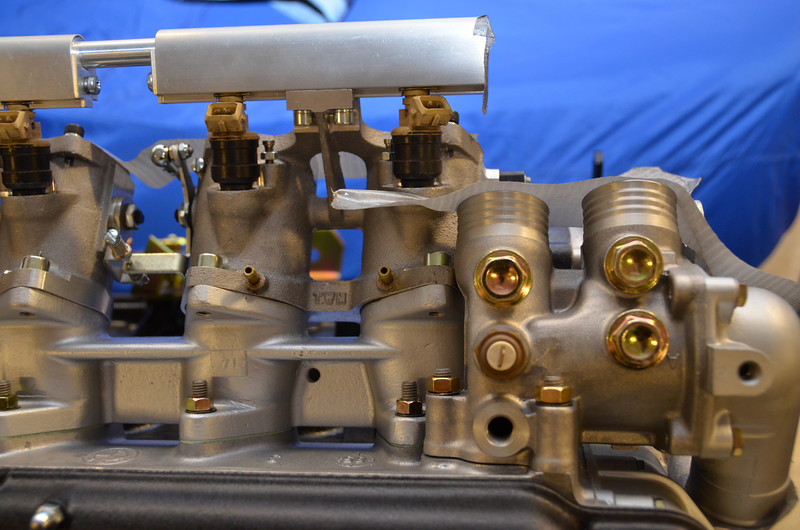 As seen in this image, the rear coolant manifold  stub is too close to the injector boss so we'll need to fabricate an extension. See details in a later image.