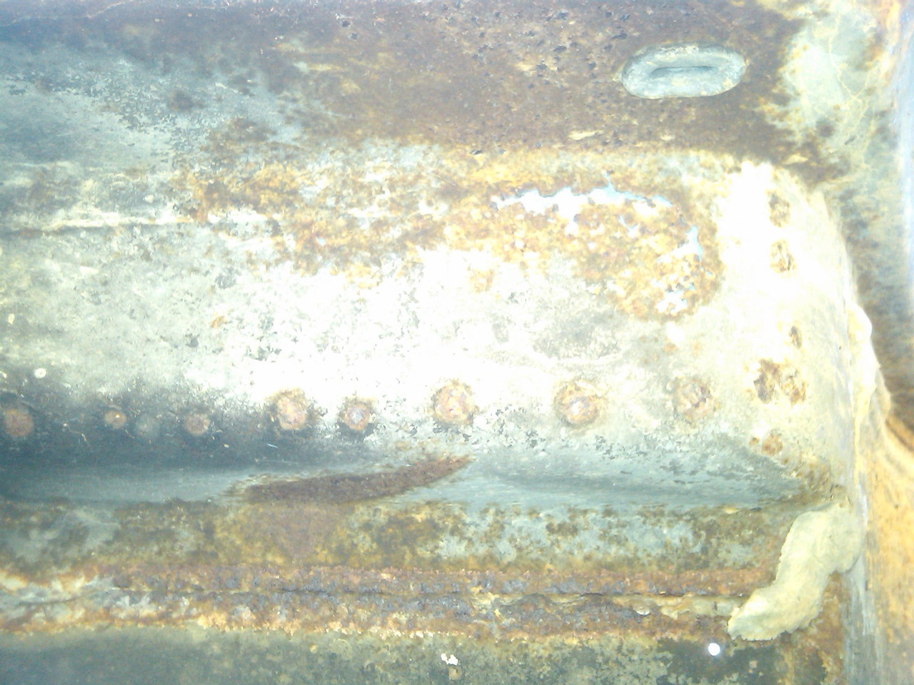 Beneath the Driver's side footwell. Rust penetration visible in both directions. Klassic Fab reproduces this section, possible cut and weld replacement?