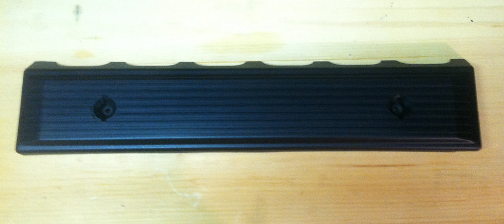 Plastic M50 fuel rail cover after stripping and painting with Rustoleum black textured paint.
