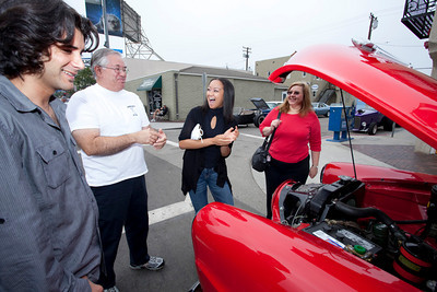 Car Show 024 - 9/12/2010: From left, Daniel Darbani, Al Castillon, Dana Powers and Elaine Castillon discuss the inner working of a 1951 Studebaker on display at the 21st Belmont Shore Car Show. mccormackphotography.com