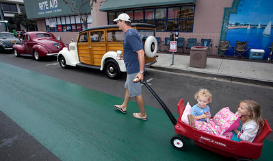 Car Show 008 - 9/12/2010: Michael Kollin of Long Beach pulls his children, Kevin and Olivia, in a red wagon on an early Sunday donut run and early bird look at the cars on hand for the 21st annul Belmont Shore Classic Car Show. mccormackphotography.com