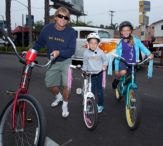Car Show 029 - 9/12/2010: Brad Thompson of Long Bech and his daughters, Samantha (7) and Hailey (10) arrived at the Belmont Shore Car Show early enough to ride their bikes down Second Street, a task that would have been virtually impossible an hour later. mccormackphotography.com