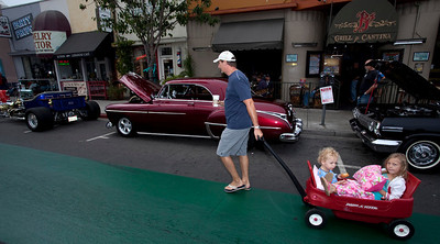 Car Show 007 - 9/12/2010: Michael Kollin of Long Beach pulls his children, Kevin and Olivia, in a red wagon on an early Sunday donut run and early bird look at the cars on hand for the 21st annul Belmont Shore Classic Car Show. mccormackphotography.com