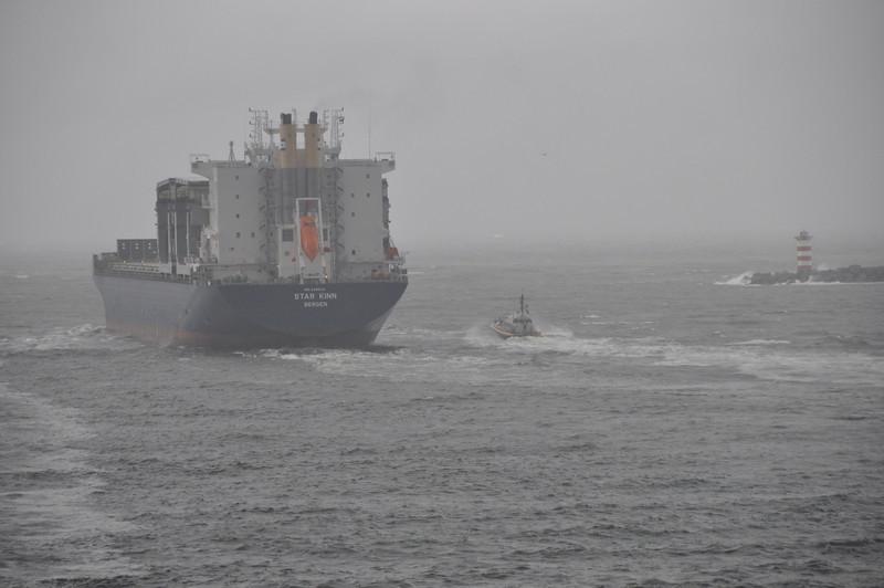 Schip dat uitvaart; loodsboot erbij om de loods straks weer terug te brengen