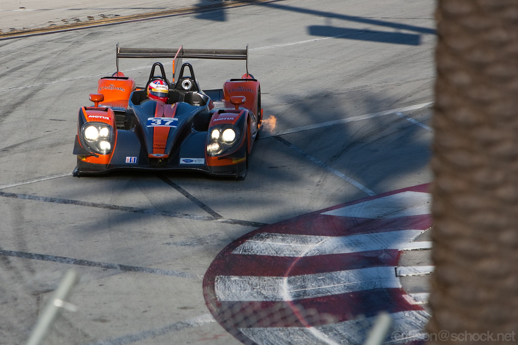 The #37 P2 belches some fire as Martin Plowman steers through Turn 1 during the 2012 ALMS Long Beach race.