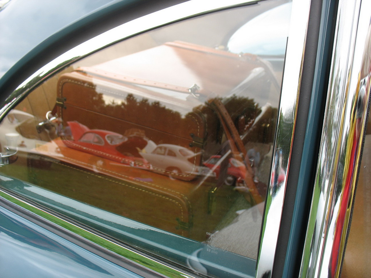 Porsche luggage strapped into the back of an early car. Also interesting reflections.