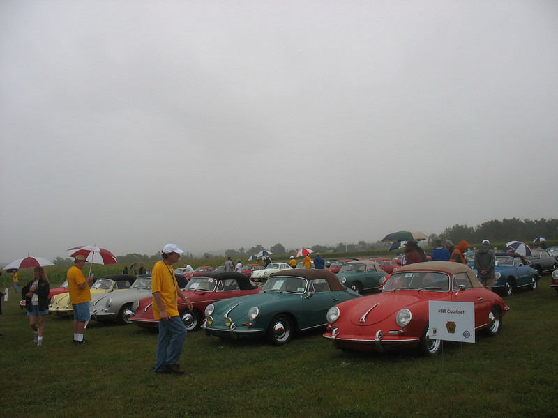 """The car show was held at the Grimes Airfield at the Golden Age Air Museum.  <a href=""""http://www.goldenageair.org/"""">http://www.goldenageair.org/</a><br /> <br /> By the time the cars were assembled, the effects of Tropical Storm Hanna were being felt and it was raining lightly. We tried to view all the cars, but didn't get pictures of all. This is a row of 356B Cabriolets."""