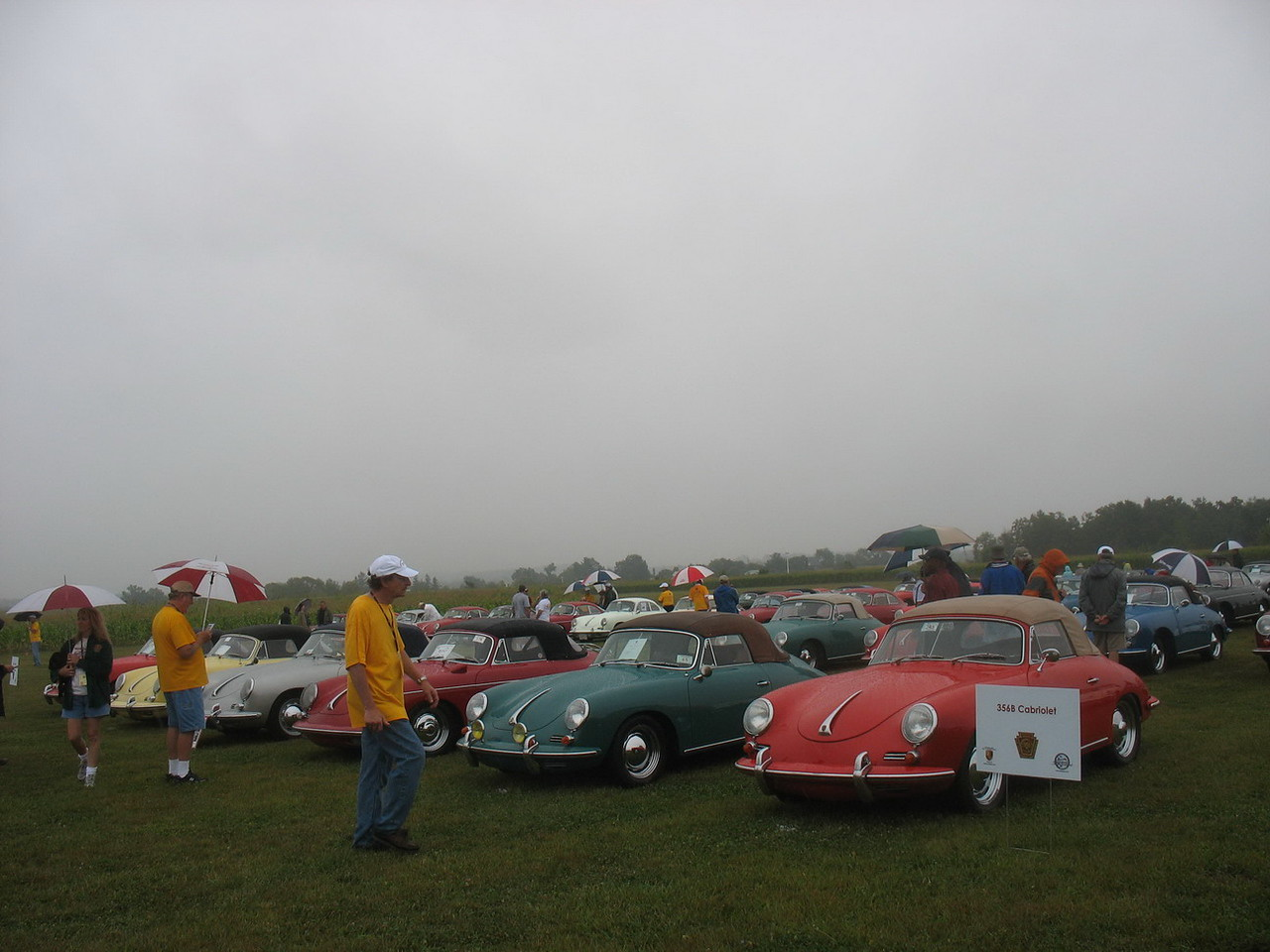 "The car show was held at the Grimes Airfield at the Golden Age Air Museum.  <a href=""http://www.goldenageair.org/"">http://www.goldenageair.org/</a><br /> <br /> By the time the cars were assembled, the effects of Tropical Storm Hanna were being felt and it was raining lightly. We tried to view all the cars, but didn't get pictures of all. This is a row of 356B Cabriolets."