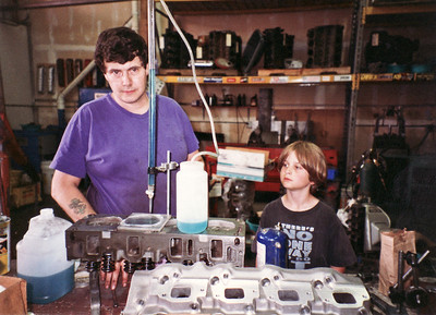 Original 16-bolt Cobra Jet heads (C8OE-6090-N) with reconditioned valve seats and new stainless steel valves. Wade measures the combustion chamber volume by adding fluid to the combustion chamber with liquid from a graduated buret. Plexiglass plate is sealed to the cylinder head with grease to prevent overflow as chamber fills up with liquid. The change in volume from beginning to end is read with the volumetric marks on the side of the buret. Edelbrock aluminum intake manifold in foreground.