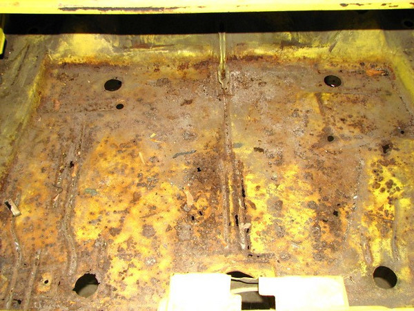 OEM trunk pan with rust holes.
