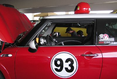 "At the hotel, the popular Boot (trunk) and Bonnet (hood) Show is held one level below the top, due to the light rain. Randy Webb, as seen through the windows of his ""mule."" Randy is an expert MNI tuner and is well-known throughout the country. He's based here in Littleton and a co-founder of MINI5280."