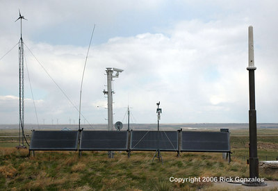 Notice the remote-controlled video camera in the center. Several radio and satellite antennae, weather measurement devices, as well as a solar panel are located on the northern end of the facility. Notice the wind electric generators on the horizon, to the left.