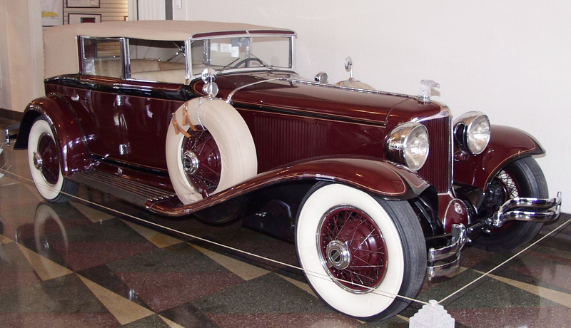 The Cord L-29 was introduced in the fall of 1929 as America's first mass-produced front wheel drive automobile. The rationale seemed to be a viable one for the introduction at that time. E.L Cord needed a vehicle to fill the price gap between the popularly priced Auburn and the grand Duesenberg. This would give the Cord Corporation wider market coverage. The idea for front wheel drive was not a new one, but it was gaining wide public attention through the victories at  the Indianapolis 500, Race car engineers including Cornelius Van Ranst and lndy driver Leon Duray were involved with the project. Chief engineer Herb Snow laid out the industry's first X-frame design for the chassis. In addition, Alan Leamy designed the beautiful bodies. The end result was a long and low vehicle which many consider to be among the most beautiful of the era.<br /> The 1930 Cord L-29 is powered by a 299 cubic inch Lycominq in-line eight-cylinder engine which produces 125 horsepower. The wheelbase measures 137.5 inches. This Front Drive Cord Phaeton was priced at $3285. <br /> In December of 1930 an Art Deco masterpiece, the Chrysler Building, opened to the public. Designed by William Van Alen, it has a striking steel spire and a sleek streamlined forms. As the effect of the 1929 stock market crash continued to be felt 1,352 banks closed during 1930.<br /> Exhibited through the courtesy of Richard and Carol Greene.