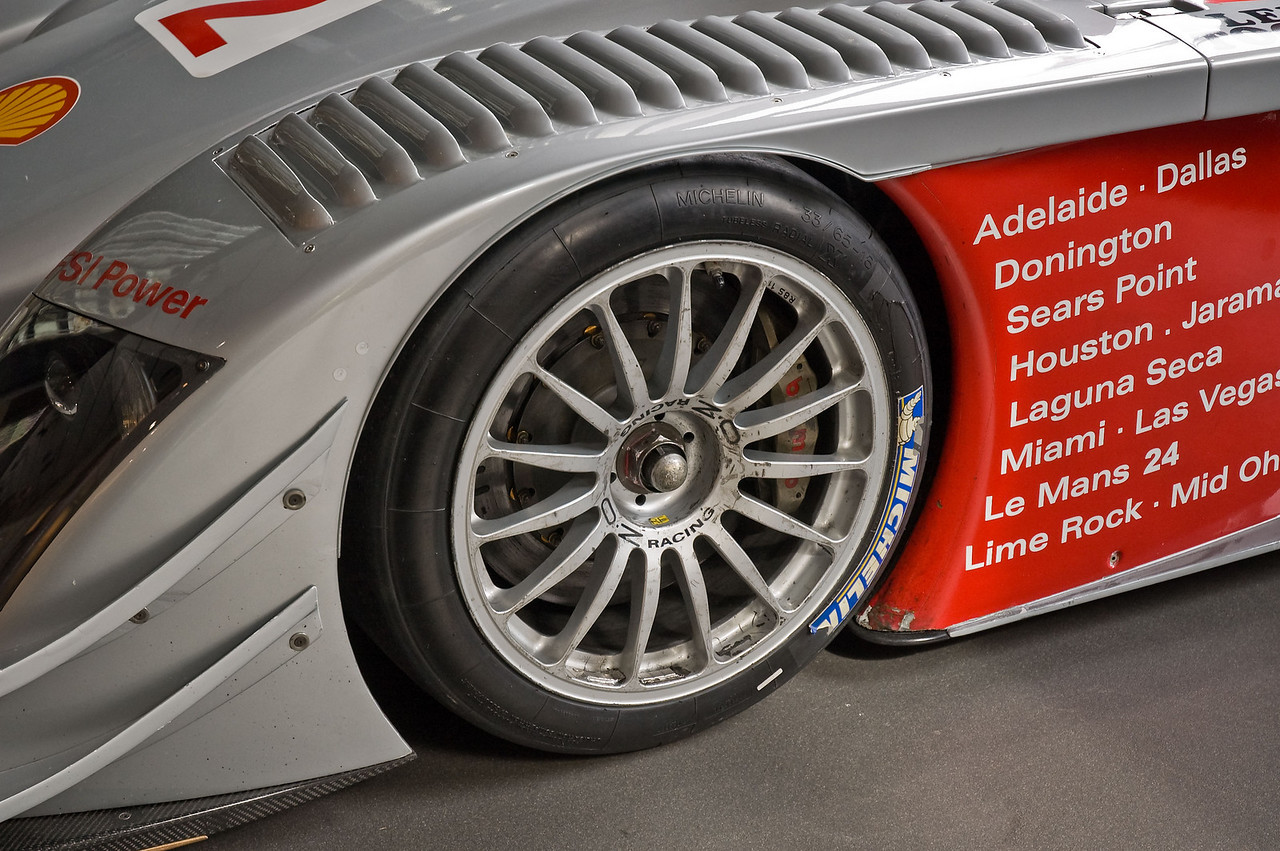 Driver's side front wheel. Notice the louvers on top of the fender. The louvers allow air to vent out of the wheel well helping to create down force.