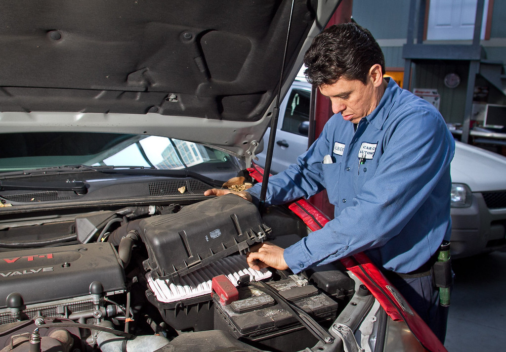 Automotive technician Alberto Teran checks out the battery for a customer who is traveling for the holidays in Oakland , Calif., on Tuesday, December 20, 2011.