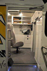 This is a view from the main entrance into the work area on the passenger side of the vehicle. We have a Panasonic Tough Book mounted on the desk. There is a file drawer and a pencil drawer below the computer. The black panel behind the computer turns work station lights on as well as the fan. The seat swivels, slides forward and backwards and reclines. In certain positions the seat can be a little hard to get around. The seat is also bolted to the floor and does not move