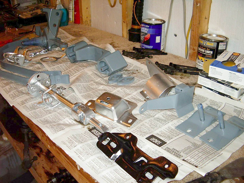 A shot of the spindle, axle dog bone, gas tank straps, quad shock brackets, steering shaft, pinion snubber bracket, fuel filter bracket and hood latch bracket all painted up after sand blasting and primer.