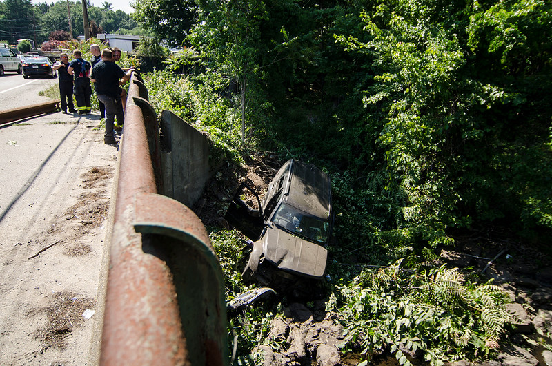 A driver was transported to HealthAlliance Hospital in Leominster with minor injuries on Wednesday afternoon after trying to pass another car where Airport Road meets Crawford Street. The driver lost control on the car, crashing into a telephone pole before rolling over a bridge and into the river. SENTINEL & ENTERPRISE / Ashley Green
