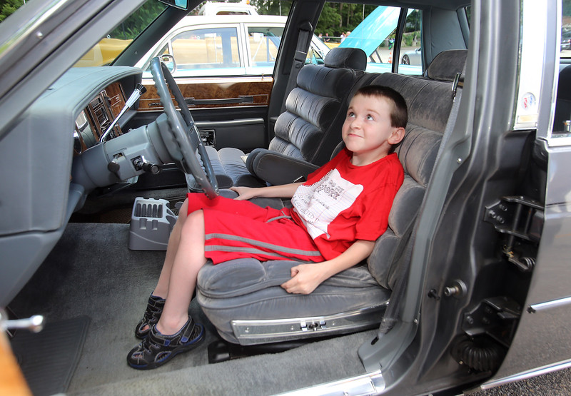 "Cars & Cans Car Show, organized by 16-year-old Alex ""Slimey"" Lambert of Dracut, to collect food and raise money for the Dracut Food Pantry. Michael O'Grady of Dracut, who turns 11 next Saturday, checks out the interior of a 1985 Buick LeSabre Collectors Edition belonging to Tom Sawyer of Dracut. (SUN/Julia Malakie)"