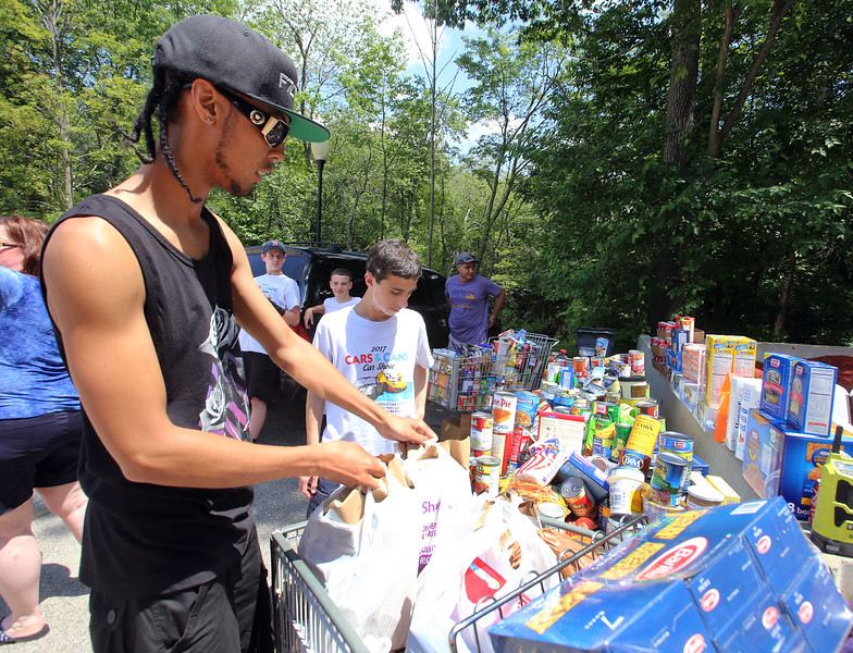 "James Rodrigues of Roxbury drops off food at the Cars & Cans Car Show, organized by 16-year-old Alex ""Slimey"" Lambert of Dracut, center, to collect food and raise money for the Dracut Food Pantry. Rodriguez heard about the event through the flier and a friend, and came with his Nissan GTR. (SUN/Julia Malakie)"