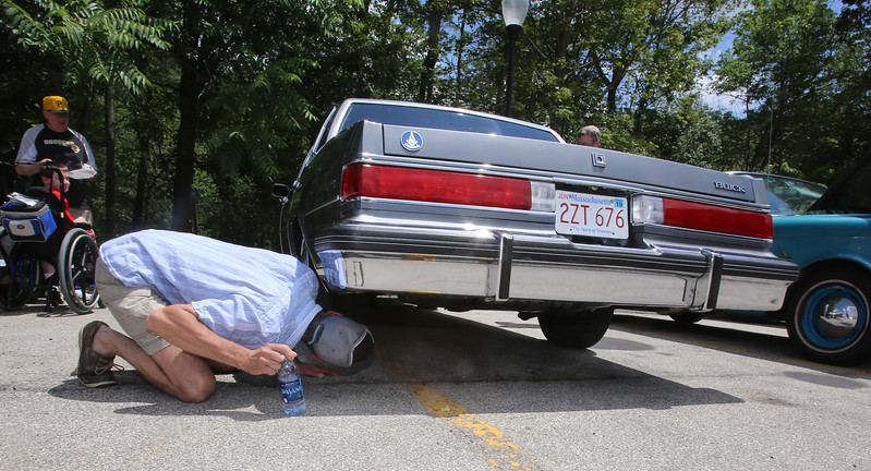 """Cars & Cans Car Show, organized by 16-year-old Alex """"Slimey"""" Lambert of Dracut, to collect food and raise money for the Dracut Food Pantry. Steve Masse of Dracut checks the undercarriage of a 1985 Buick LeSabre Collectors Edition that Tom Sawyer of Dracut bought a week ago with just 12,000 miles on it, confirming what Sawyer said: """"it's never seen a winter."""" Sawyer bought it from a dealer who'd bought it at an estate sale. (SUN/Julia Malakie)"""