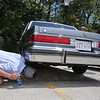 "Cars & Cans Car Show, organized by 16-year-old Alex ""Slimey"" Lambert of Dracut, to collect food and raise money for the Dracut Food Pantry. Steve Masse of Dracut checks the undercarriage of a 1985 Buick LeSabre Collectors Edition that Tom Sawyer of Dracut bought a week ago with just 12,000 miles on it, confirming what Sawyer said: ""it's never seen a winter."" Sawyer bought it from a dealer who'd bought it at an estate sale. (SUN/Julia Malakie)"