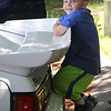 "Cars & Cans Car Show, organized by 16-year-old Alex ""Slimey"" Lambert of Dracut, to collect food and raise money for the Dracut Food Pantry. Zack Jemlich, 4, of New Ipswich, N.H., hangs off the rear spoiler of Lambert's 1988 Saleen Mustang. (SUN/Julia Malakie)"