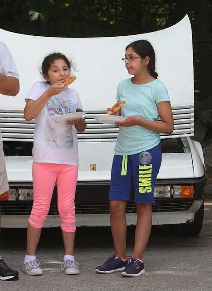 "Cars & Cans Car Show, organized by 16-year-old Alex ""Slimey"" Lambert of Dracut, to collect food and raise money for the Dracut Food Pantry. Sofia Perez, 8, and her sister Alani Perez, 13, of Dracut, eat pizza in front of a 1984 Ferrari belonging to Gloria Sesin De Contreras of Windham, N.H. (SUN/Julia Malakie)"