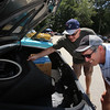 "Cars & Cans Car Show, organized by 16-year-old Alex ""Slimey"" Lambert of Dracut, to collect food and raise money for the Dracut Food Pantry. Tom Sawyer, rear, show Steve Masse the trunk of the 1985 Buick LeSabre Collectors Edition he just bought a week ago with 12,000 miles on it. It came with several spare air filters. Both are from Dracut. (SUN/Julia Malakie)"