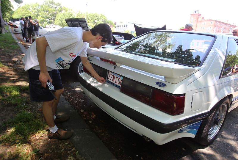 "Cars & Cans Car Show, organized by 16-year-old Alex ""Slimey"" Lambert of Dracut, to collect food and raise money for the Dracut Food Pantry. Lambert removes a bit of debris from the license plate holder on his 1988 Saleen Mustang. Saleen is the company that upgraded it. (SUN/Julia Malakie)"