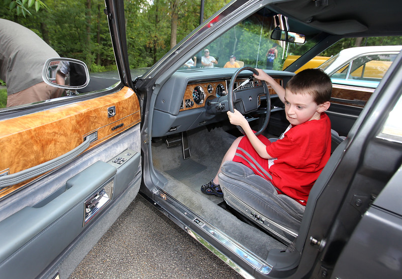 "Cars & Cans Car Show, organized by 16-year-old Alex ""Slimey"" Lambert of Dracut, to collect food and raise money for the Dracut Food Pantry. Michael O'Grady of Dracut, who turns 11 next Saturday, turns the wheels of a 1985 Buick LeSabre Collectors Edition belonging to Tom Sawyer of Dracut. (SUN/Julia Malakie)"