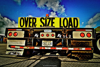 Over size load  truck in a sheet metal warehouse parking lot.