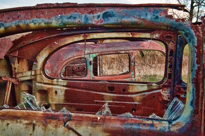 Through the window of an old Ford is its mate nearby, a second 1940's vintage Ford.