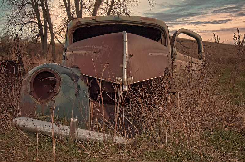 A 1940 Ford Tudor Deluxe has been partially stripped of useable parts, and then parked, left to rust east of Wilton.  This car represents the peak of early Ford Motor Company days.  About this time, the company reorganized and the designer of this style of car, Edsel Ford, son of Henry, was forced out.