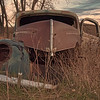 A 1940-ish Ford has been partially stripped of useable parts, and then parked, left to rust east of Wilton.
