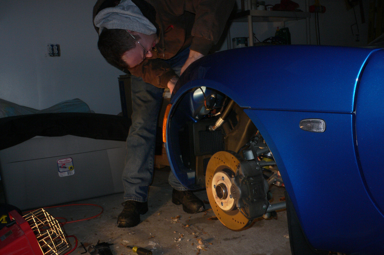 A couple of weeks after the install of the interior pieces, (and in euqually cold winter weather)we're back at it. Today we will be installing some blue LEDs to replace the daytime running lights which are currently incandescent. To access the headlight assembly, you must first take the front wheel off.