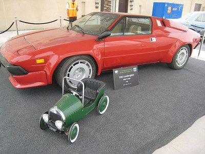 A custom designed single seater convertible with all the accessories expected in an exclusive one-off vehicle, including white wall tyres and luxurious upholstery.  In the background is a red car.
