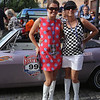 Vintage cars participating in The Great Race arrive in Lowell and park on Middle Street, on their way from Maine to Florida. Driver Karen Stumb of Chattanooga, right, and her navigator, daughter Whitney Brown, 15, stand by Stumb's 1965 Corvair. They are dressed in '60s style outfits for the event. (SUN/Julia Malakie)