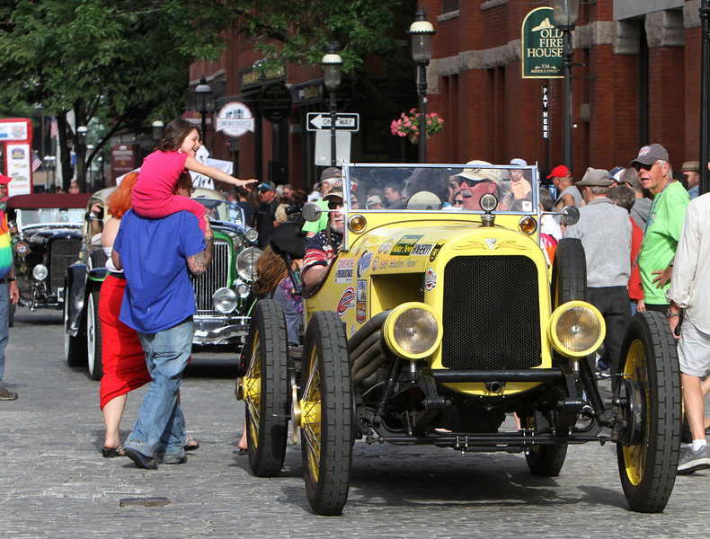 Vintage cars participating in The Great Race arrive in Lowell and park on Middle Street, on their way from Maine to Florida. A little girl waves as navigator Tom Coad of Santa Ana, Calif., and driver Don Mussche of Brea, Calif., pass in a 1916 Hudson Indy Racer. (SUN/Julia Malakie)