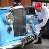 """Vintage cars participating in The Great Race arrive in Lowell and park on Middle Street, on their way from Maine to Florida. Neal Patton of Jackson, Miss.,cleans the road dust off his 1954 Bentley, which he's only had for 10 months, and bought to do the Great Race. Last year's race stopped in Vicksburg, and he met some of the participants in a bar and """"got the bug"""" from talking to them. (SUN/Julia Malakie)"""