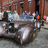 """Vintage cars participating in The Great Race arrive in Lowell and park on Middle Street, on their way from Maine to Florida. Joe LaFreniere of Chelmsford, right, takes a picture of a """"tribute"""" (copy) of a 1937 Bugatti. There are only two originals left.  (SUN/Julia Malakie)"""