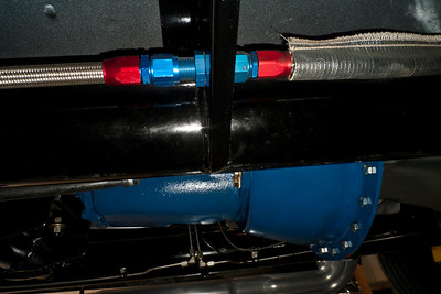 "Recirculating fuel system passes through chassis outriggers with anodized AN fittings and SS braided hose. Heat shielding fabric covers fuel lines that run into the engine bay (right). Stainless brake lines and fittings are visible mounted on the far main chassis tube (4"" diameter powder coated steel). Toploader transmission and Lakewood scattershield are painted Ford engine blue."